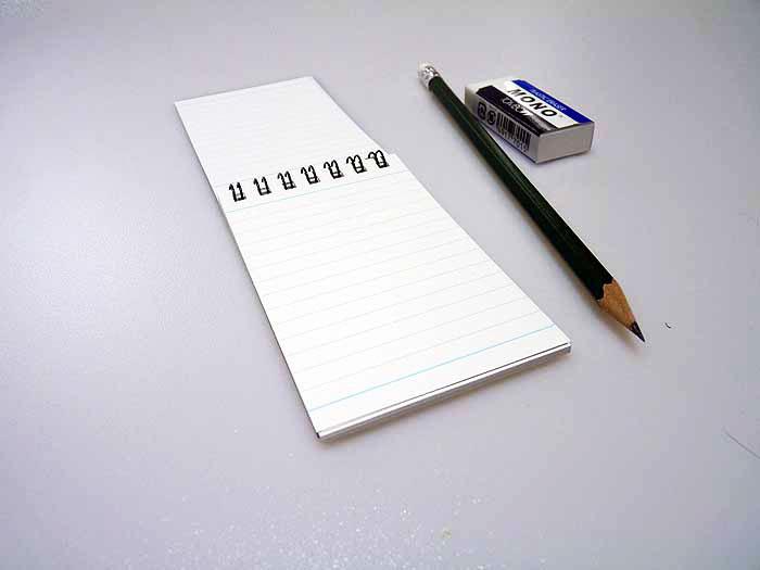 開いたメモ帳と鉛筆とケシゴムの拡大写真