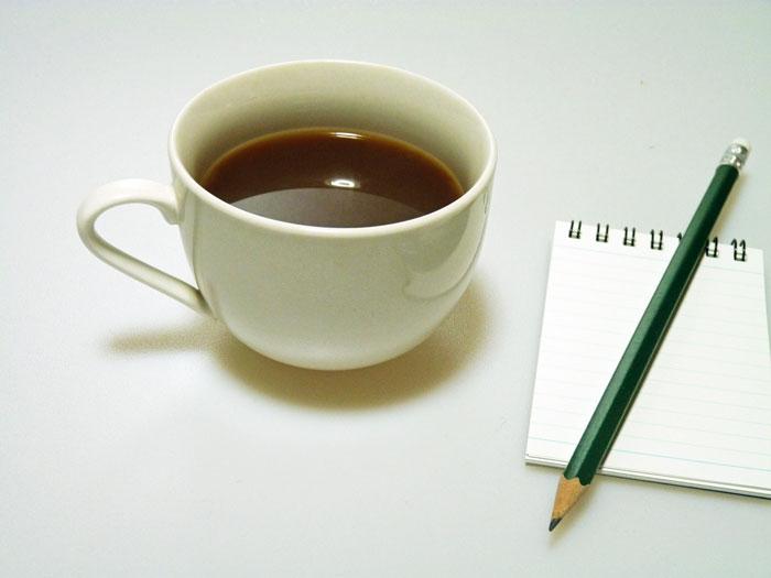コーヒーと鉛筆とメモ帳の拡大写真