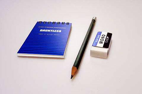 閉じたメモ帳と鉛筆とケシゴムの拡大写真