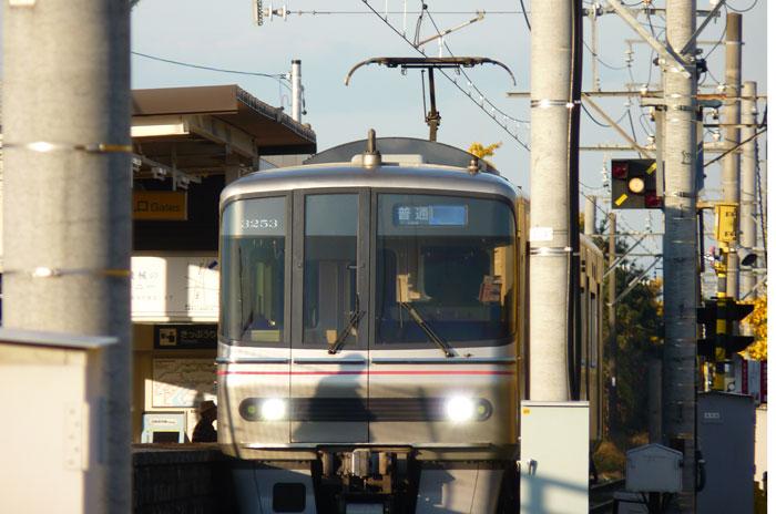 駅に入ってきたシルバーの電車の拡大写真