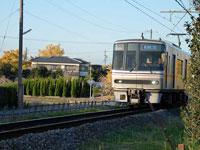 走るシルバーの電車と青い空