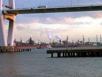 橋の下から見える工場と白い煙と海