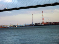 斜張橋の下から見える工場と紅白の煙突と海