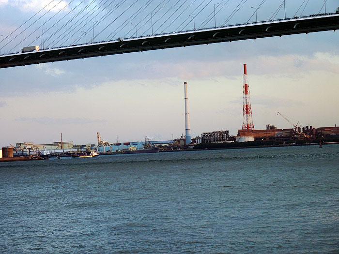 斜張橋の下から見える工場と紅白の煙突と海の拡大写真