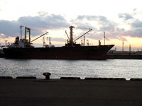 夕暮れ時の海と黒と赤の大きな船