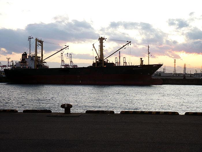 夕暮れ時の海と黒と赤の大きな船の拡大写真