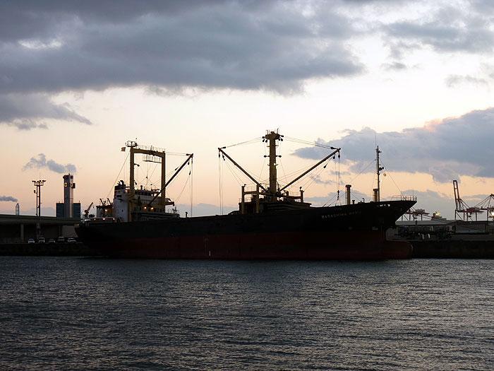 港に停泊する大きな赤と黒の船と海の拡大写真