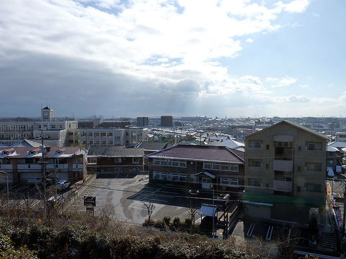 屋根に雪が残る家と町の冬景色の拡大写真