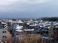 枯れ木と町の雪景色