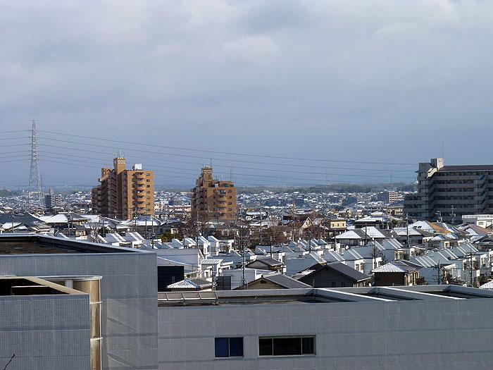 マンションと雪で真白な町の冬景色の拡大写真