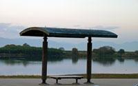 公園のベンチと川の風景