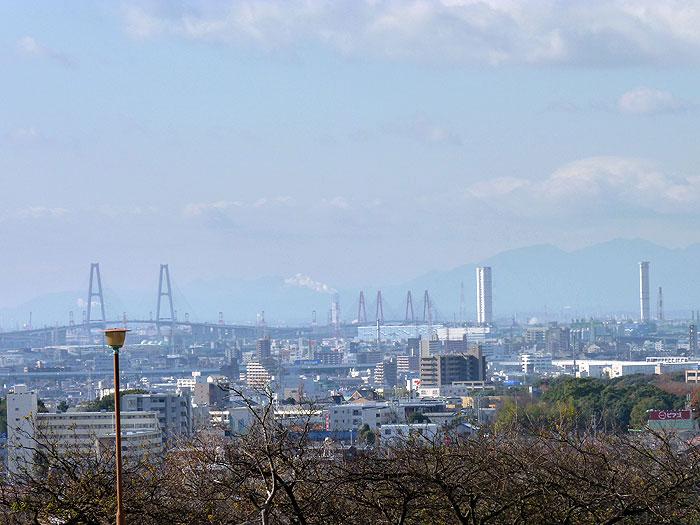 白みがかった町と空のと枯れ木群の冬景色の拡大写真