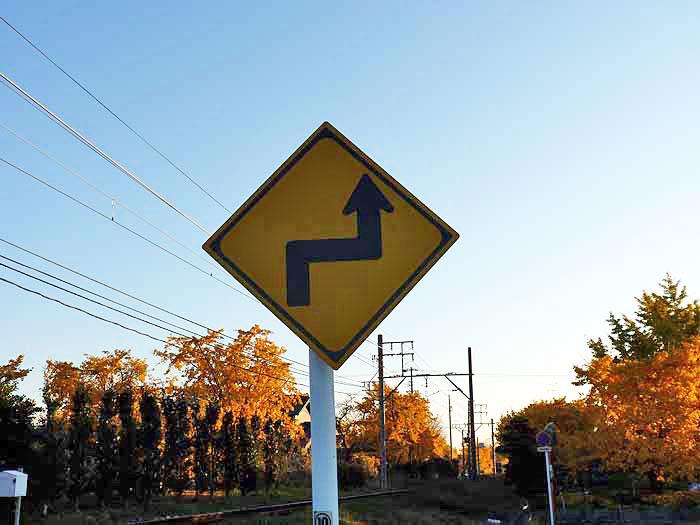 道路標識(右背向屈折あり)と青い空の拡大写真
