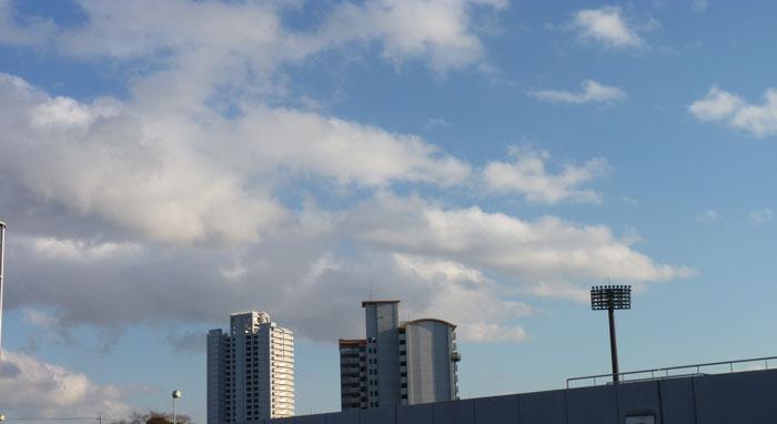 青い空と白い雲とマンション2棟・スタジアムの照明の拡大写真