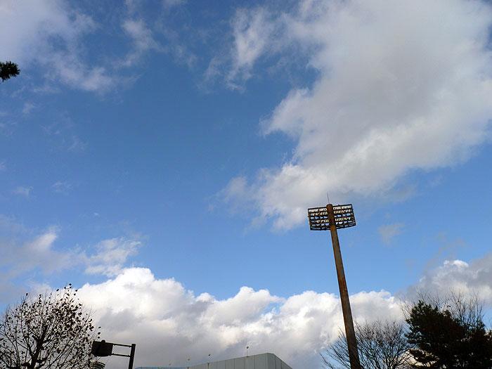 青い空と白い雲、サッカー場の照明の拡大写真