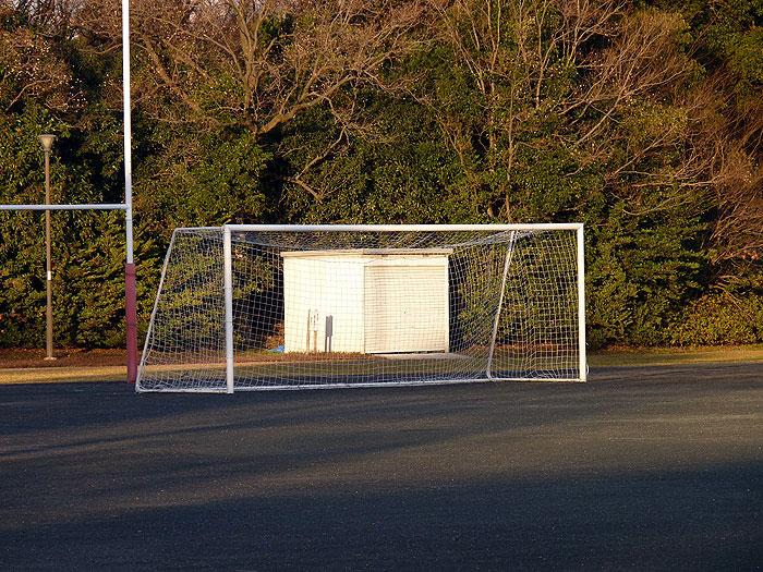夕日が差し込むサッカー場とゴールネットの拡大写真