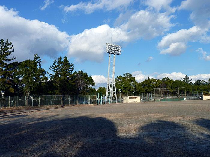 野球のグラウンドと青い空白い雲緑の木々の拡大写真