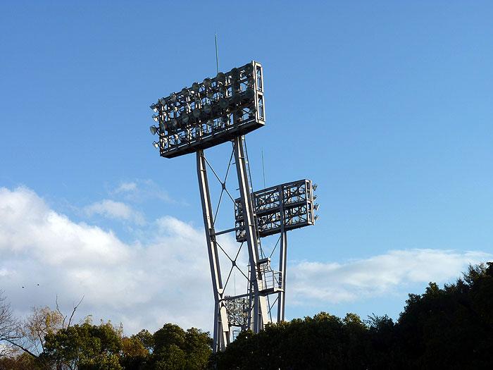 野球場の照明と青い空白い雲緑の植物の拡大写真