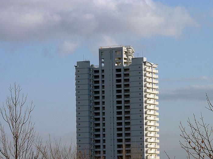 白い高層マンションと青い空の拡大写真
